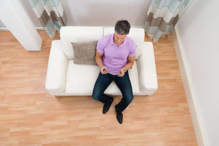 angle views: High Angle View Of Man Sitting On Couch Using Digital Tablet