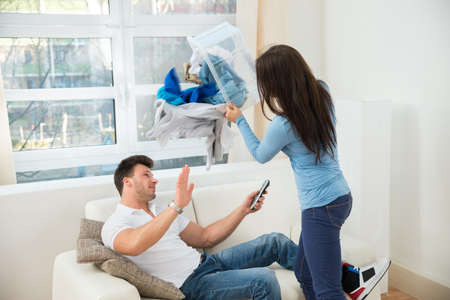 clean clothes: Woman Throwing Laundry On Lazy Husband Sitting On Sofa