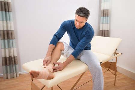 pies masculinos: Hombre que se sienta en la cama que mecanografía elástico vendaje en el pie Foto de archivo