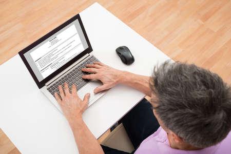 Opinión de alto ángulo de un hombre Preparación Reanudar en la computadora portátil Foto de archivo - 40751532