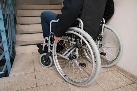 silla de ruedas: Primer plano de hombre con discapacidad en silla de ruedas delante de la escalera Foto de archivo