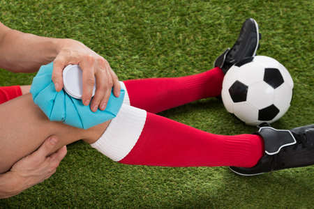 Close-up Of A Soccer Player Icing Knee With Ice Pack On Field
