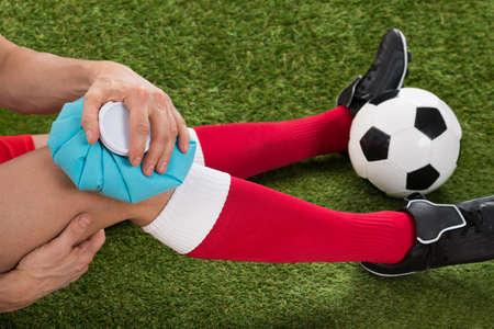 Primer plano de una rodilla Jugador de Fútbol formación de hielo con bolsa de hielo en Campo Foto de archivo - 40870630