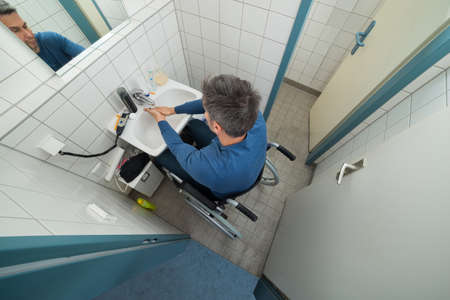 High Angle View Of Man On Wheelchair Washing Hands In Bathroom