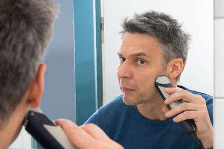 electric trimmer: Portrait Of A Man Looking In Mirror Trimming Beard