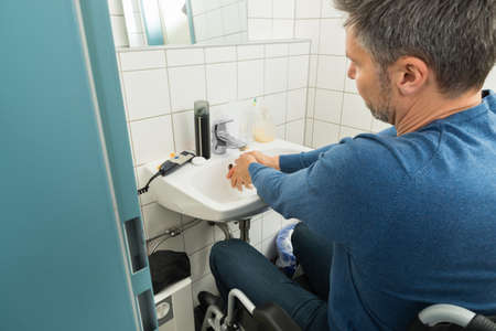 Close-up Of Man On Wheelchair Washing Hands In Bathroom