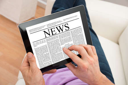 Close-up Of Man Reading News On Digital Tablet At Home photo