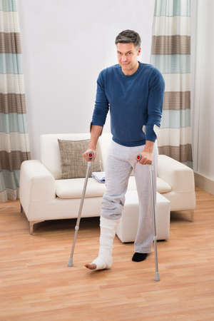 broken leg: Portrait Of A Disabled Man Using Crutches For Walking At Home Stock Photo