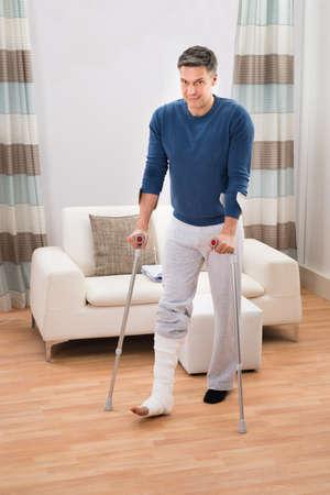 pierna rota: Retrato de un hombre lisiado usando muletas para caminar en el hogar Foto de archivo