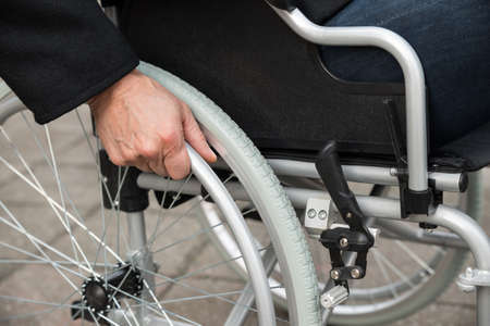 outdoor chair: Close-up Of Disabled Man Sitting On Wheelchair Stock Photo
