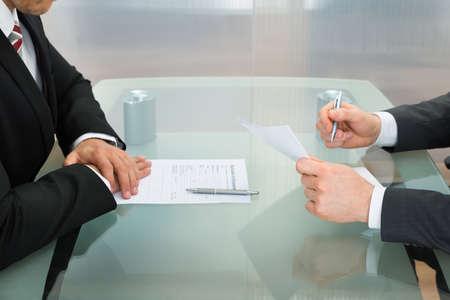 entrevista de trabajo: Empresario realización de una entrevista de trabajo con formulario de solicitud en el escritorio de oficina