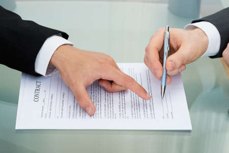 Person Pointing On Paper To Sign On Contract Foto de archivo
