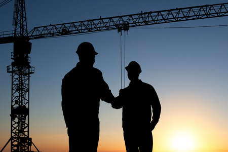 site: Silhouette Of Two Architect At Construction Site Shaking Hand Stock Photo