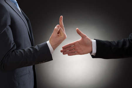 reject: Close-up Of A Person Trying To Shake Hand With A Person Showing Fuck Gesture Stock Photo