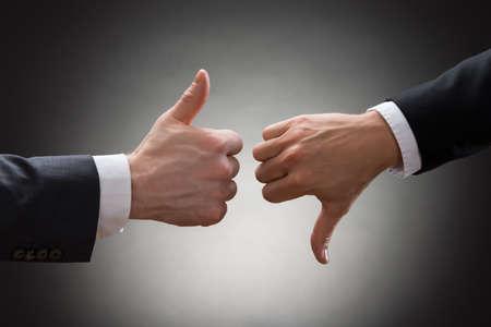 desacuerdo: Primer plano de dos manos Empresarios que muestra el pulgar para arriba y pulgar abajo sesión