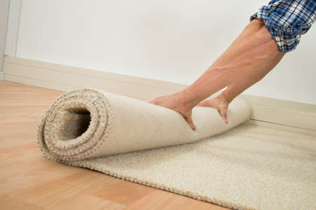 Close-up van een mannelijke Arbeider Folding tapijt op de vloer thuis Stockfoto - 40871193