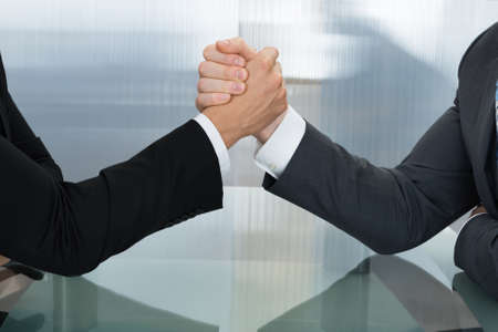 wrestling: Two Businessman Holding Each Other Hands Over Desk In The Office
