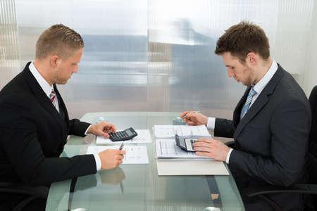 calculadora: Dos hombre de negocios c�lculo Bills j�venes usa la calculadora en el lugar de trabajo