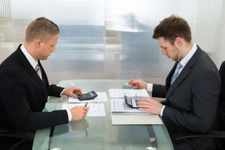 calculator: Two Young Businessman Calculating Bills Using Calculator At Workplace