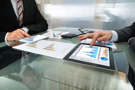 デジタル タブレットの 2 つの実業家分析グラフのクローズ アップ 写真素材