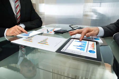 BUSINESSMEN: Close-up Of Two Businessman Analyzing Graph On Digital Tablet