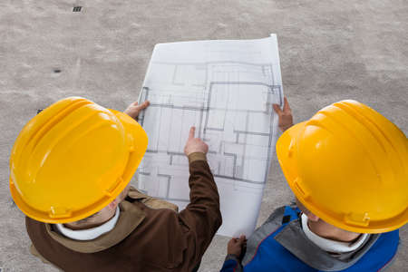 High Angle View Of Two Architects Discussing Blueprint