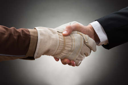 Close-up Of Worker Wearing Glove Shaking Hand With Businessman