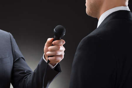 media equipment: Close-up Of A Reporter Conducting Interview Of Businessman