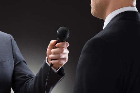 reportero: Primer plano de un reportero que conducen entrevista del hombre de negocios