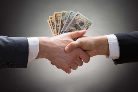 remuneraciones: Primer plano de dos empresarios agitando las manos con dinero