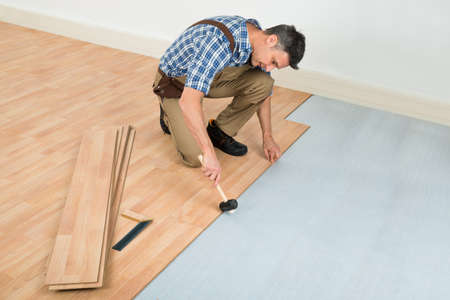 laminated: Carpenter Installing New Laminated Wooden Floor At Home Stock Photo