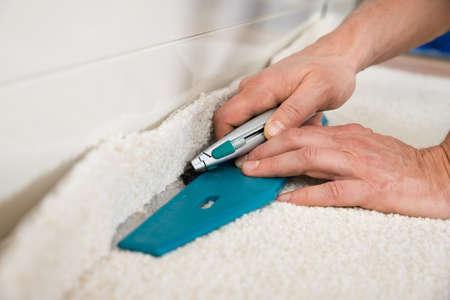 trabajando en casa: Primer plano de un artesano corte de alfombras con el cortador Foto de archivo