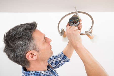 wirework: Close-up Of A Male Electrician Fixing Light On Ceiling Stock Photo