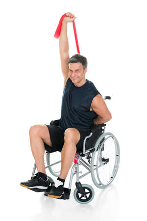 resistance: Disabled Man On Wheelchair Stretching With Resistance Band Over White Background