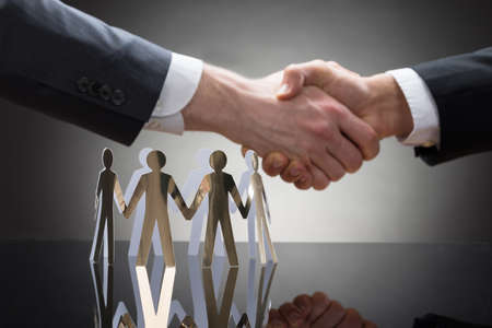 paper cutout: Close-up Of Businesspeople Shaking Hands With Paper Cutout Figures