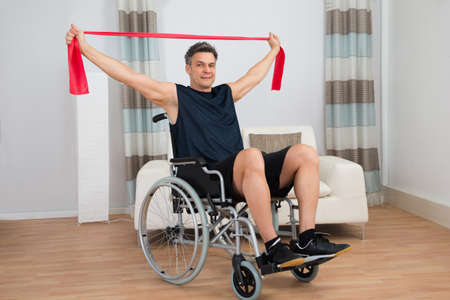 Handicapped Man On Wheelchair Exercising With Resistance Band At Home Stockfoto