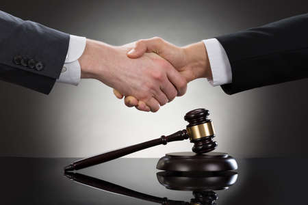 law: Close-up Of Two Businessman Shaking Hands In Front Of Mallet