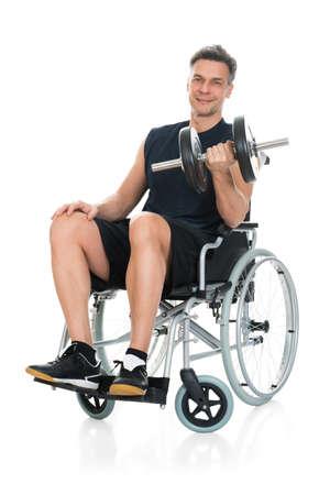 sillon: Hombre sonriente desactivado en que se resuelve con el fondo mancuernas sobre blanco con silla de ruedas
