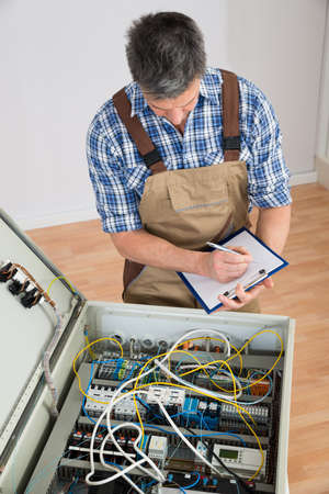meter box: Electrician Looking At Fuse Box Holding Clipboard