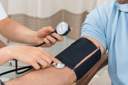 Close-up Of Female Doctor Checking Blood Pressure Of Male Patient Stock Photo