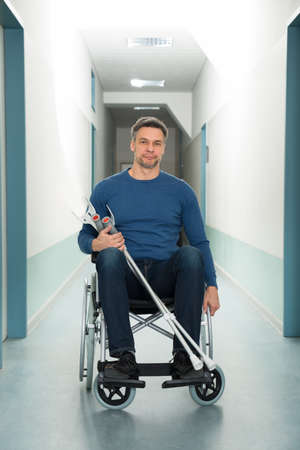 wheel house: Portrait Of Mid-adult Man Sitting On Wheelchair With Crutches