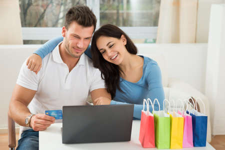 shopping online: Portrait Of A Happy Young Couple Shopping Online At Home