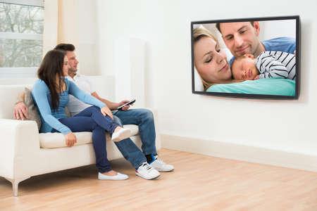 リビング ルームのテレビを見てソファの上に座っている若いカップル 写真素材