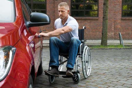 person sitting: Retrato De Un Hombre Sentado En discapacitados Puerta de apertura con silla de ruedas de un coche Foto de archivo