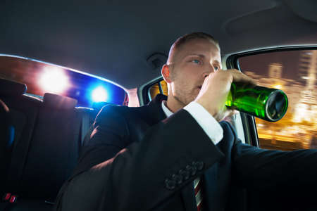 pulled over: Portrait Of A Young Man Drinking Beer Chased By Police