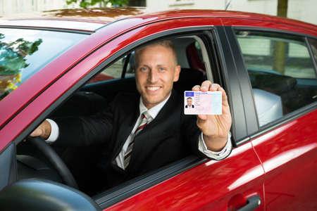Portret Młodych Biznesmen Pokazano Jego Prawo jazdy Od Otwartego Okna Samochodu