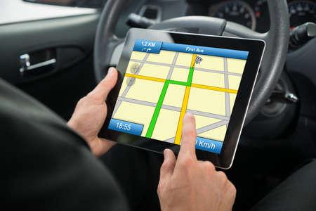 person sitzend: Close-up von einer Person in einem Auto sitzt mit Hilfe von GPS-Service Auf Tablet PC