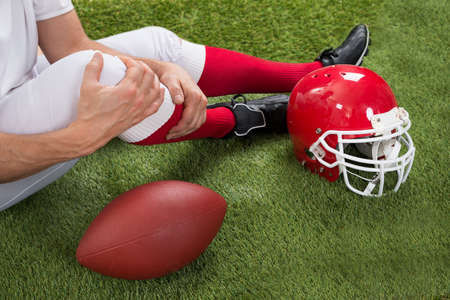 leg injury: Close-up Of Injured American Football Player On Field Stock Photo