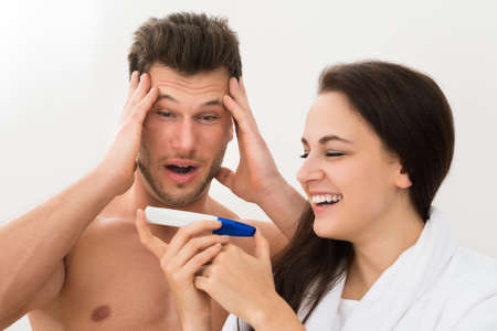 pregnancy test: Portrait Of Young Couple Looking At Pregnancy Test Over White Background