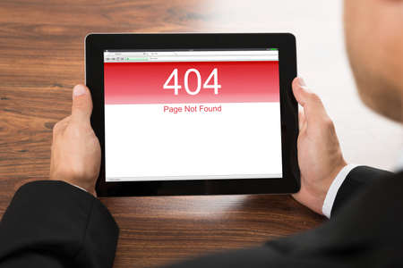 error message: Close-up Of A Businessman Holding Digital Tablet With Error Message On Screen Stock Photo